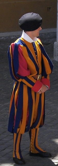 Photo Credit: https://commons.wikimedia.org/wiki/File:Swiss_Guard_near_Basilica_di_San_Pietro.jpg